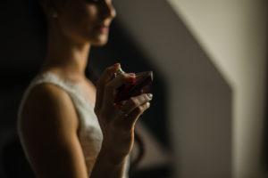 la mariée se mettant du parfum pendant les préparatifs